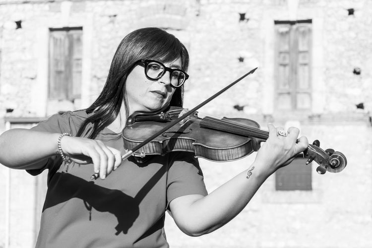 Musical Instrument Music One Person Real People String Instrument Violin Musician Young Adult Musical Equipment Holding Playing Arts Culture And Entertainment Leisure Activity Young Women Artist Front View Glasses Eyeglasses  Lifestyles Waist Up Skill  Bow - Musical Equipment Violinist Hairstyle