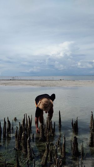 Man bending in sea against sky