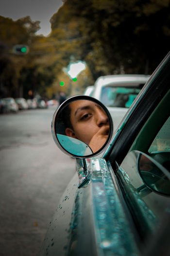 Portrait of young man reflecting on side-view mirror while traveling in car