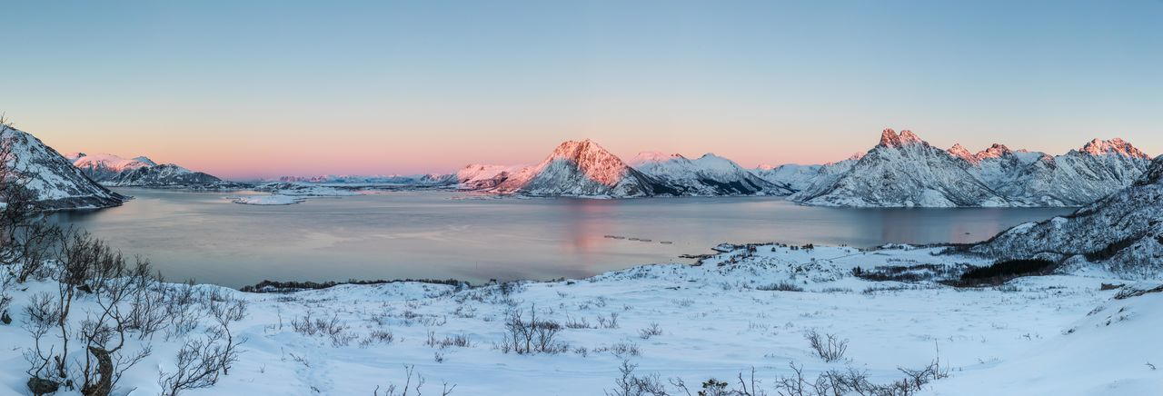 Panoramic shot of river by snowcapped mountains against sky during sunset