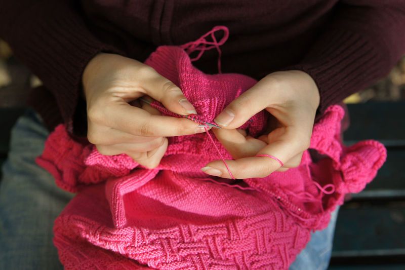 Midsection Of Woman Knitting Pink Wool