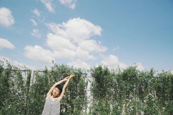 Girl doing yoga against plants covered fence