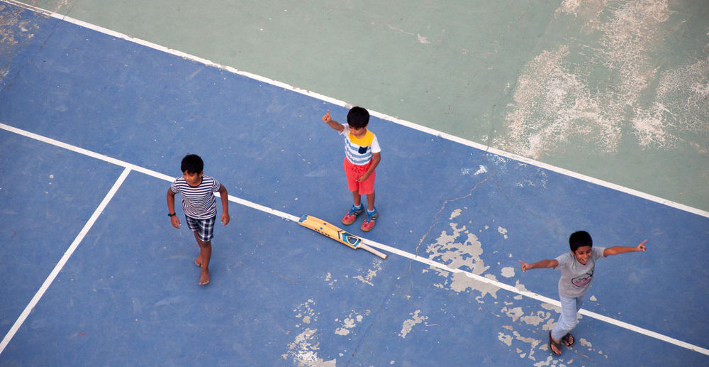 High angle view of children playing on umbrella