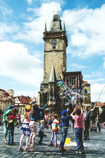 Battle Of The Cities Architecture Built Structure Building Exterior Clock Tower Tower Large Group Of People Sky Person Tourist Lifestyles Cloud Travel Destinations Embrace Urban Life History Children Cloud - Sky Famous Place Bubbles Tall - High City Outdoors Square Prague People And Places