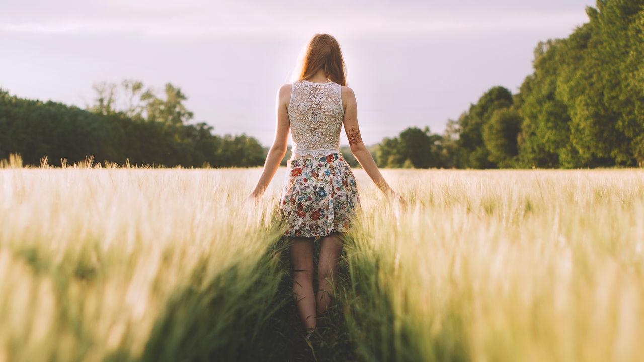 Rear view of woman walking amidst grass on field