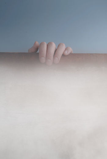 Close-up of person hand on wall against sky