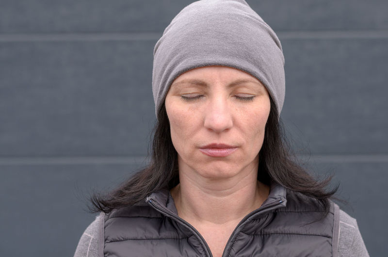 Close-Up Of Woman With Eyes Closed Wearing Knit Hat Against Wall