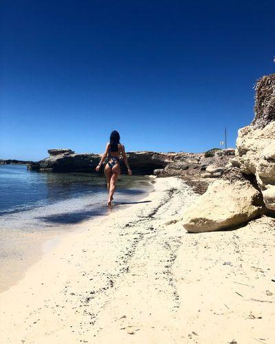 Rear view of woman in bikini walking on shore at beach against sky