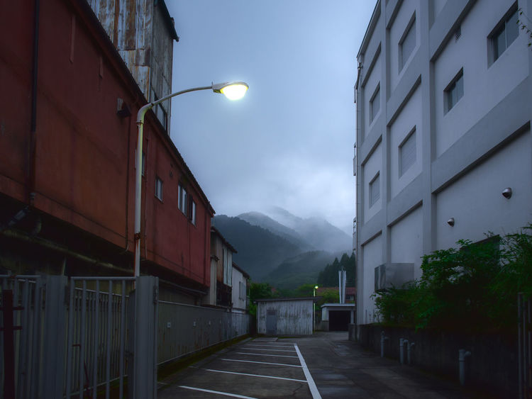 Sukima, between two buildings, in Japan, always good surprise. Nikko, Japan. 2018 Dark Darkness HUAWEI Photo Award: After Dark Japan Japanese  Nikko Building Exterior City Darkness And Beauty darkness and light Diminishing Perspective Direction Dusk Illuminated Lighting Equipment Mountain Range Nature Night No People Outdoors Residential District Road Sky Street The Way Forward