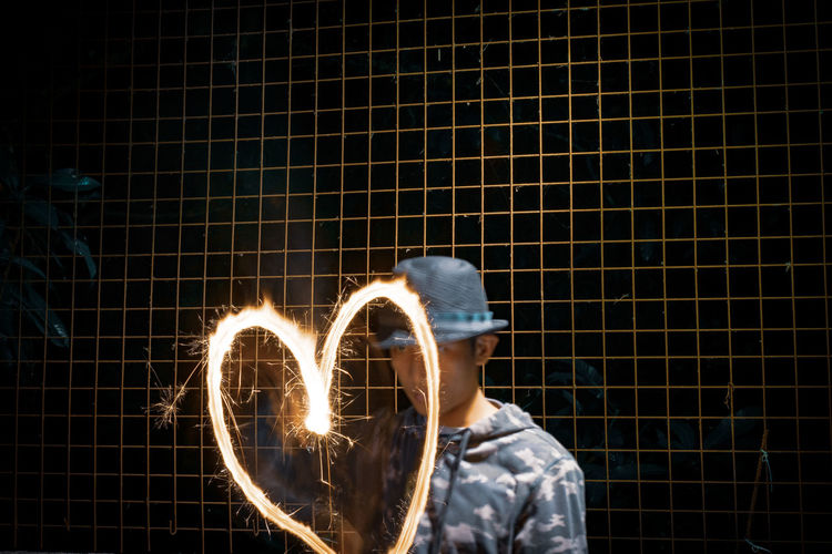 EyeEm Selects EyeEm Best Shots Heart Shape Young Men Wire Mesh Human Hand Illuminated Motion Pattern Men Love Sparkler Long Exposure Close-up Light Painting Light Trail Firework - Man Made Object Glowing 2018 In One Photograph