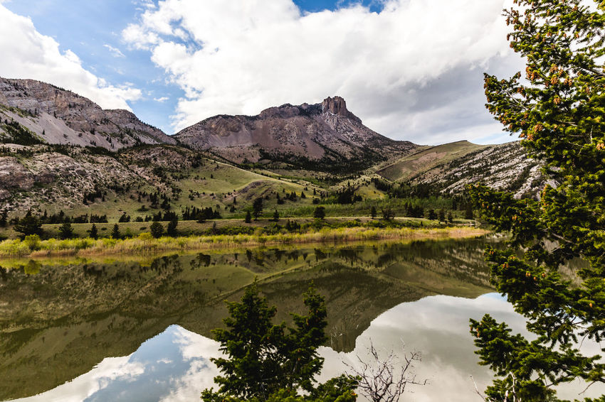 Rocky formations reflecting on water in the Lewis & Clark Wilderness near Augusta, Montana, USA. Perspectives On Nature Beauty In Nature Cloud - Sky Day Idyllic Lake Landscape Mountain Mountain Range Nature No People Outdoors Reflection Scenics Sky Tranquil Scene Tranquility Tree Water Waterfront