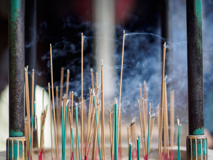 Close-Up Of Burning Incenses In Temple