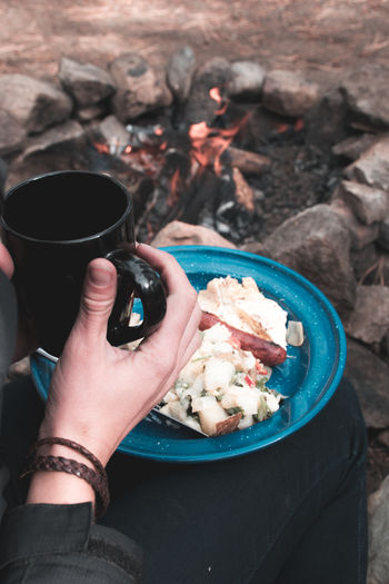 Midsection of person holding coffee cup and food at campsite
