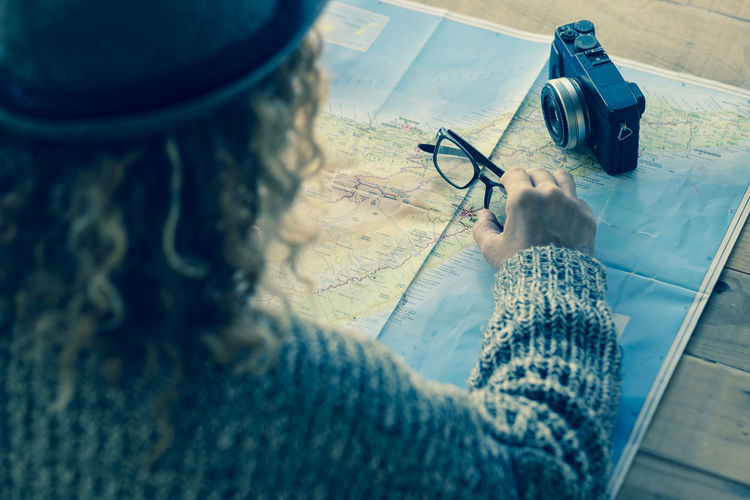 High angle view of woman holding eyeglasses on world map