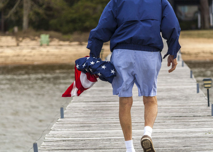 American Flag Beach Boardwalk Casual Clothing Focus On Foreground Lake Life Mobile Bay Mobile, Alabama Old Man One Man Only One Person Only Men Patriotic Real People Rear View Seersucker Sperry Walking Warf Water Windbreaker Wooden Plank Old School Classic Resist Be Brave