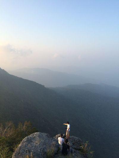 Friends At Mountain Peak Against Sky