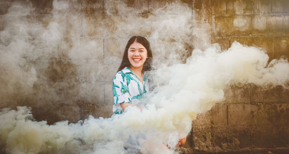 Portrait of smiling young woman amidst smoke against wall