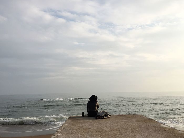 Rear view of man sitting on beach against sky