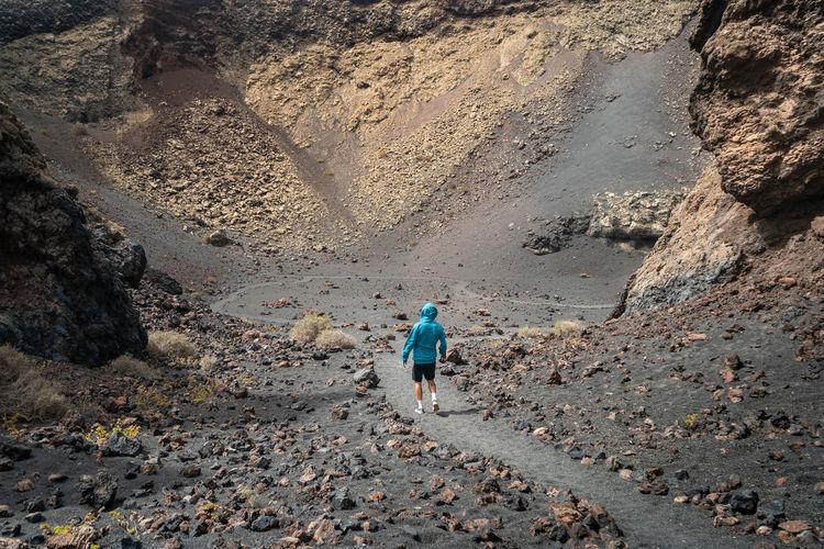 Rear view of man walking on rocks