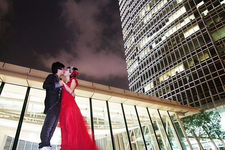 Low angle view of couple kissing at night