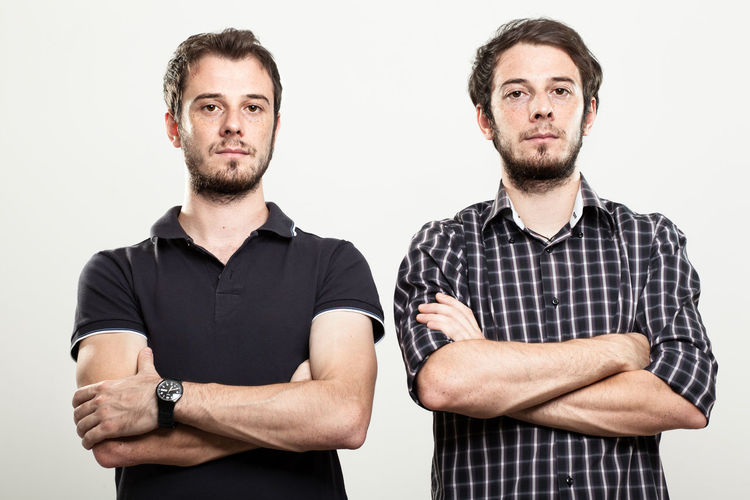 Portrait of men with arms crossed standing against white background