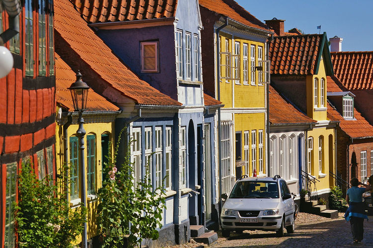 Narrow cobblestone street on the island of Aero with colorful historic residential buildings, parked car, pedestrian City Cityscape Denmark Vacations Architecture Building Exterior Built Structure Car City Cobblestone Colorful Day History House Land Vehicle Outdoors Sky Street Sunlight Timber Frame Timber-framed Townhouse Transportation Travel Destinations Urban