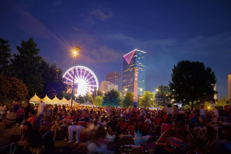 People at centennial olympic park against sky at night