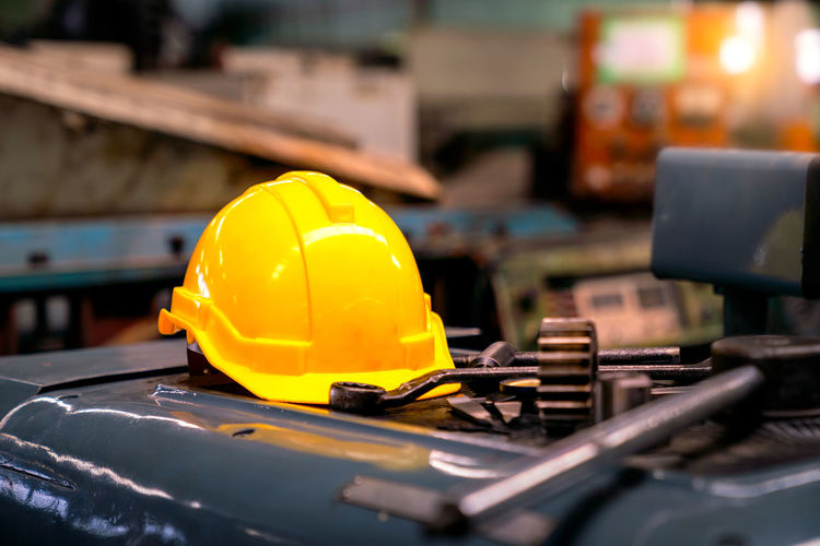Yellow helmet and industrial equipment and metal.