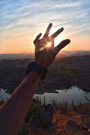 Sunbeam through hand against sky during sunset