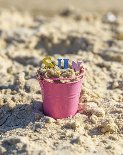 Close-Up Of Toy On Sand In Bucket At Beach