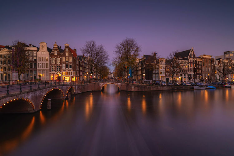 Amsterdam at evening Architecture Water Building Exterior Built Structure City Illuminated Bridge Connection Reflection River Building Night Dusk Bridge - Man Made Structure Transportation Nature Sky No People Residential District Arch Bridge Amsterdam Old Town Sunset Last Light Long Exposure