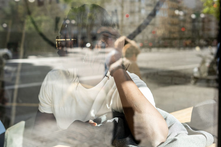 Midsection of man sitting on street in city