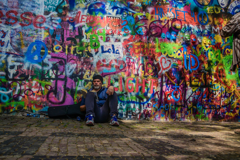 Art And Craft Casual Clothing Creativity Front View Full Length Graffiti Leisure Activity Lifestyles Looking At Camera Multi Colored One Person Outdoors Portrait Real People Sitting Teenager Wall Wall - Building Feature Young Adult Young Men