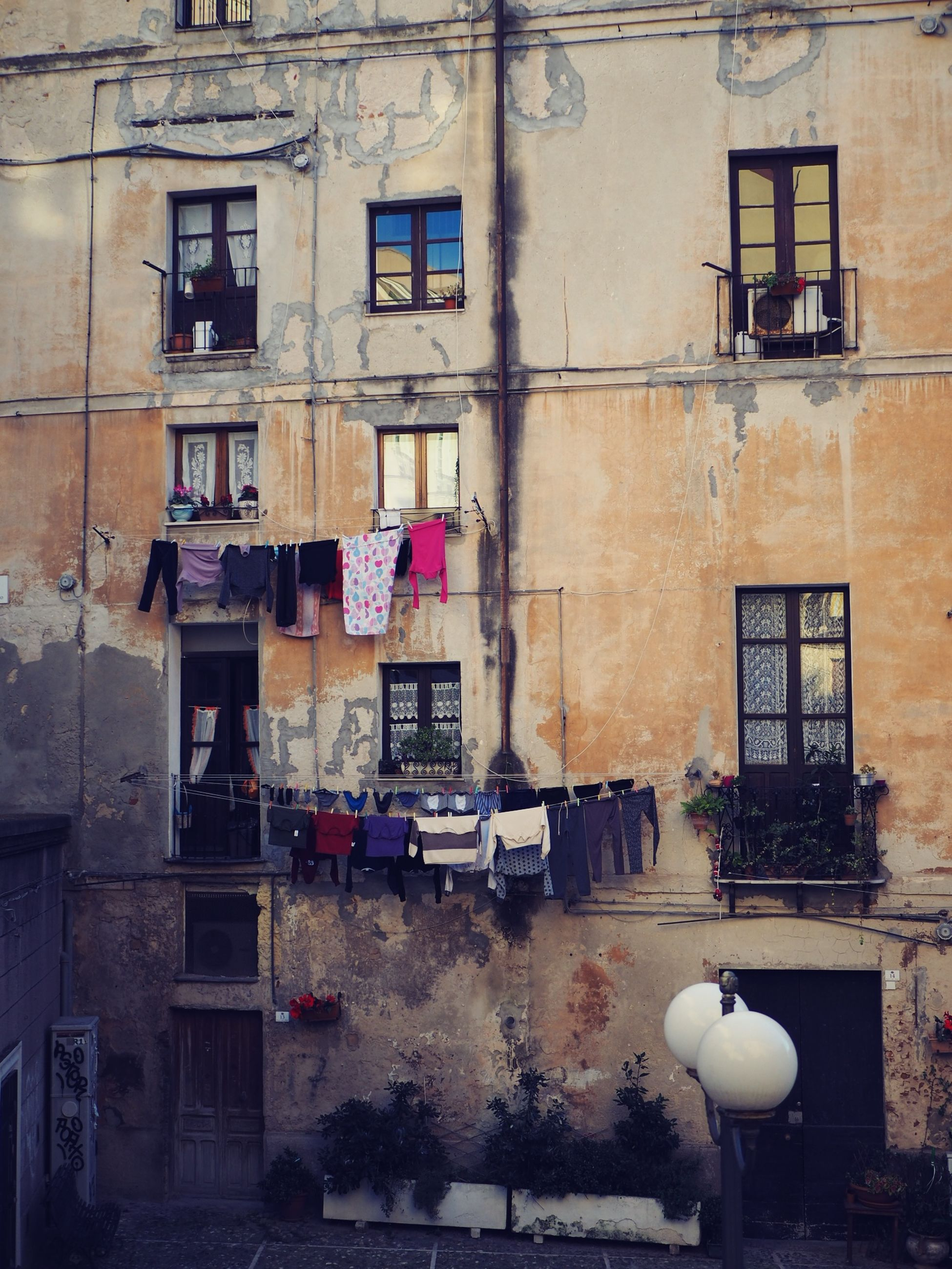 building exterior, built structure, architecture, residential district, building, window, day, city, no people, outdoors, hanging, wall - building feature, nature, wall, lighting equipment, clothing, street, house, old, weathered, apartment