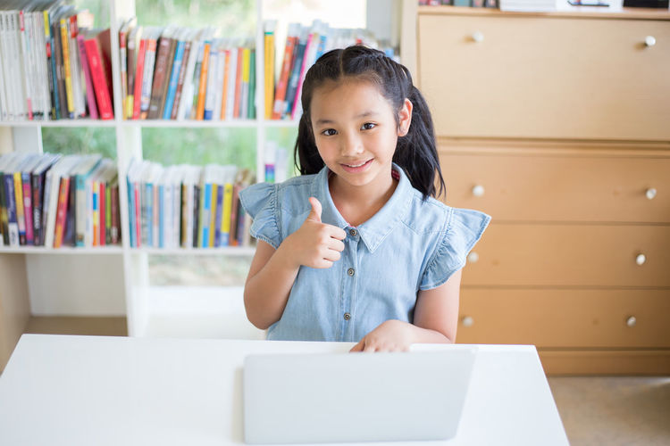 Portrait of girl gesturing thumbs up while using laptop while sitting at desk