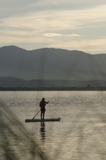Silhouette woman paddleboarding in sea