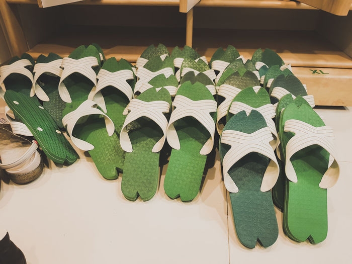 Green sandals placed in front of the cabinet. Cabinets Green Locker Sandals Slippers Wood Lined Lined Pattern Orderly Shoe Rack Slippers Lover Tidily White Wooden