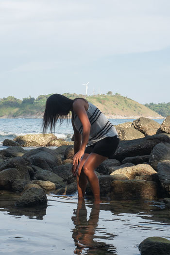 Full length of young woman on rock at sea shore against sky