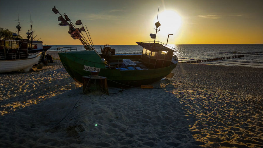 Fishing boat moored on beach against sky during sunset