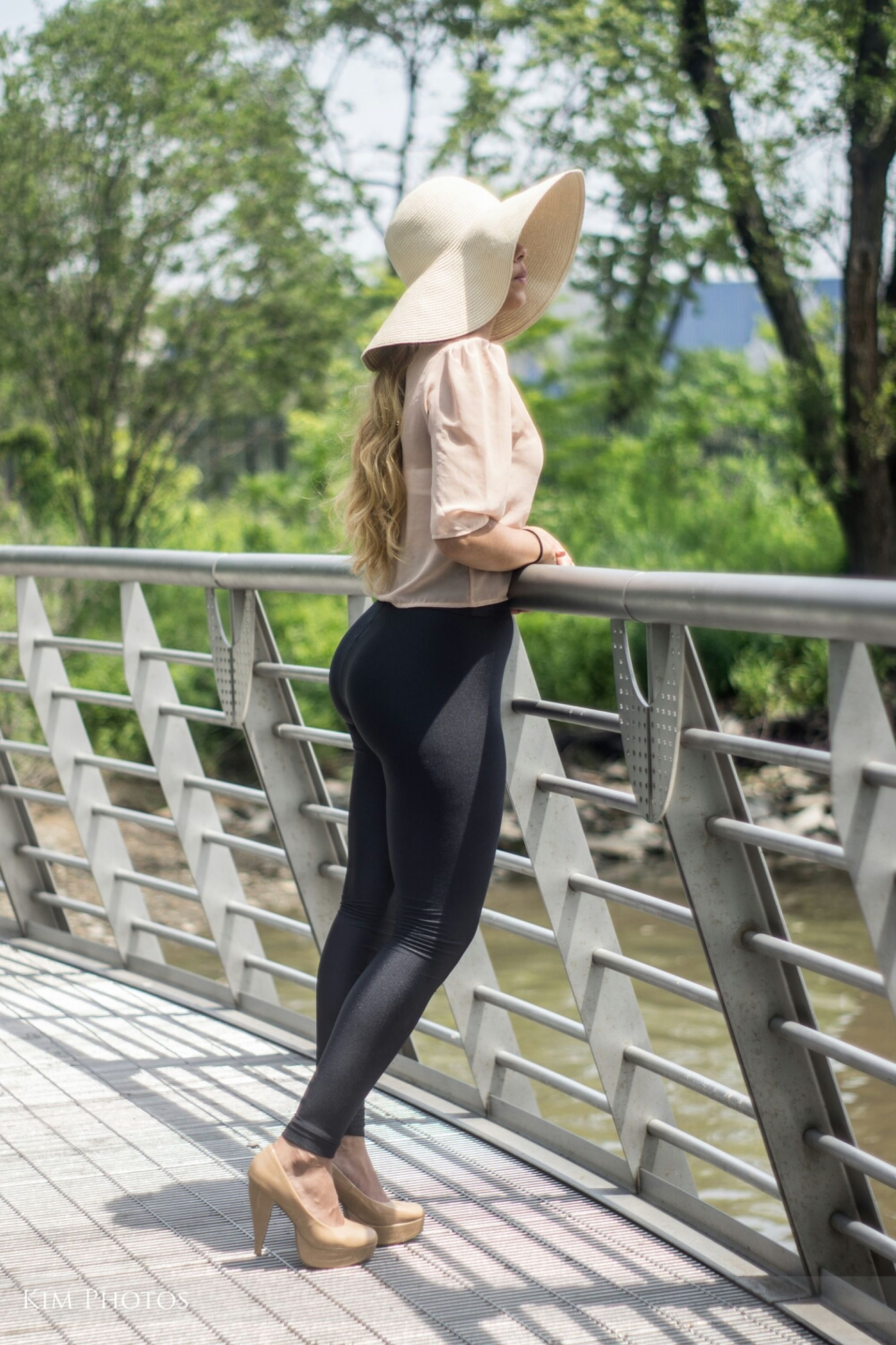 lifestyles, standing, tree, casual clothing, leisure activity, young adult, full length, young women, person, rear view, dress, long hair, railing, three quarter length, sunlight, fashion, day, low section