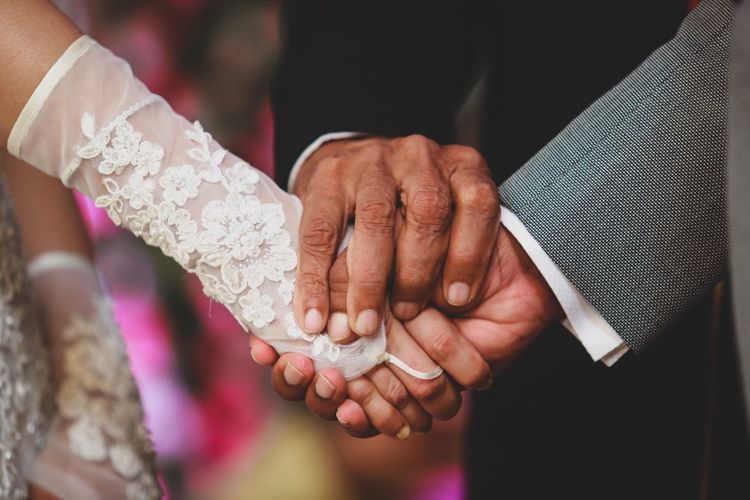 Cropped image of people holding hands at wedding ceremony
