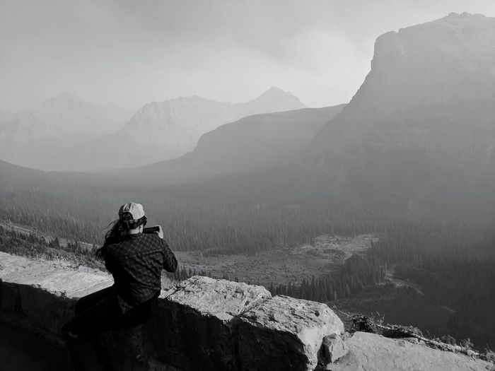 Female photographing scenic overlook along going to the sun road in glacier national park