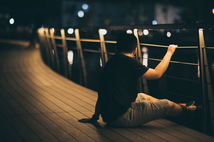 Alone in the park Real People Full Length One Person Lifestyles Rear View Leisure Activity Illuminated Night Railing Men Sitting Footpath Adult Focus On Foreground Architecture Casual Clothing Bridge Women Motion
