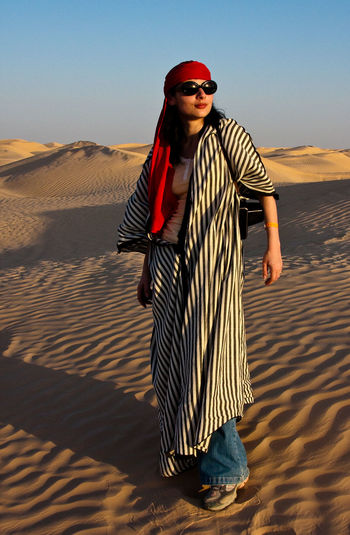 Young woman wearing sunglasses on sand in desert against sky