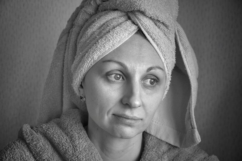 Close-up of thoughtful woman with towel against wall