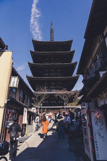 People in temple amidst buildings against sky