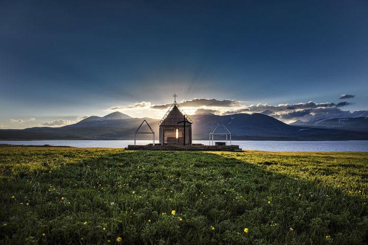 Church by sea against sky