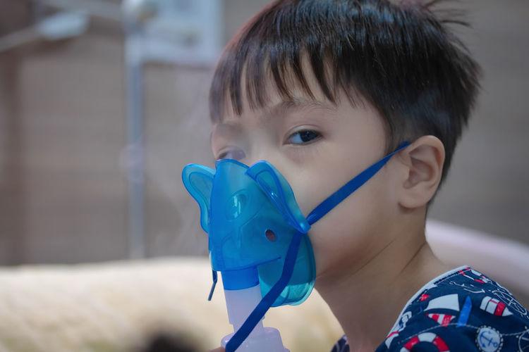Portrait of cute boy wearing oxygen mask in hospital