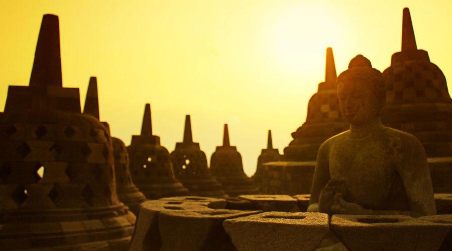 Buddha Statue Against Stupas Against Clear Orange Sky