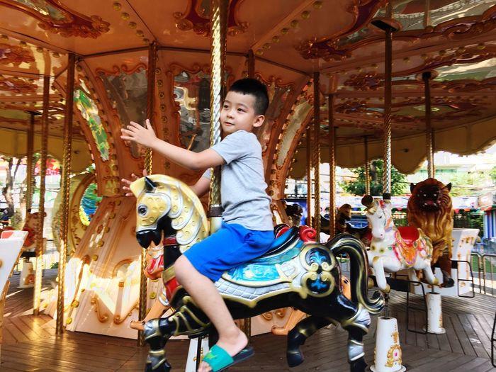 Full length of boy riding motorcycle at amusement park